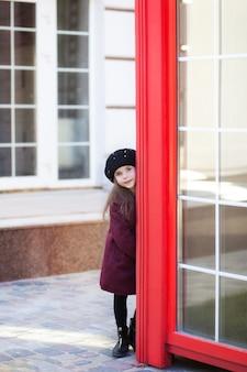 Mała wesoła dziewczyna stojąca w pobliżu czerwonej budki telefonicznej w burgundowym płaszczu i berecie. czerwona budka telefoniczna w londynie. wiosna. jesień. z międzynarodowym dniem kobiet. od 8 marca!