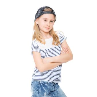 Mała wesoła dziewczyna uczennica z blond włosami i czapką kapelusz.