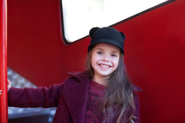 Mała wesoła dziewczyna w pobliżu czerwonego angielskiego autobusu w pięknym płaszczu i kapeluszu. mała wesoła dziewczyna w pobliżu czerwonego angielskiego autobusu w pięknym płaszczu i kapeluszu. podróż dziecka. autobus szkolny. londyn czerwony autobus.