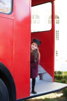 Mała wesoła dziewczyna w pobliżu czerwonego angielskiego autobusu w pięknym płaszczu i kapeluszu. podróż dziecka. autobus szkolny. londyn czerwony autobus. wiosna. z międzynarodowym dniem kobiet. od 8 marca!
