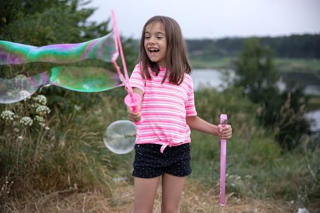 Mała wesoła dziewczynka bawi się dużymi bańkami mydlanymi w przyrodzie.