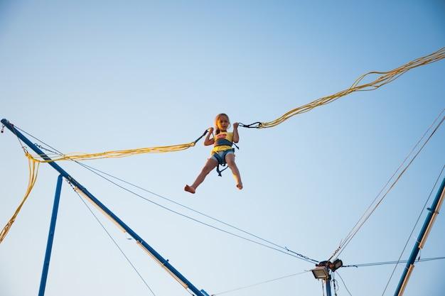 Mała wesoła dziewczynka leci na sprężystych, jasnych gumkach i wskakuje na trampolinę ciesząc się długo oczekiwanymi wakacjami w ciepłym słońcu