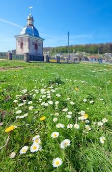 Mała wiejska kaplica na wiosennej polanie kwiatów