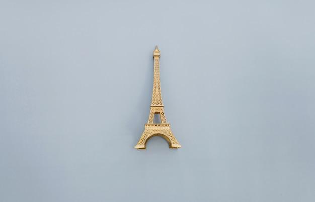 Mała wieża eiffla jako pamiątka z paryża na szarym tle.