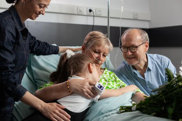 Mała wnuczka przynosząca kwiaty podczas wizyty u chorej babci