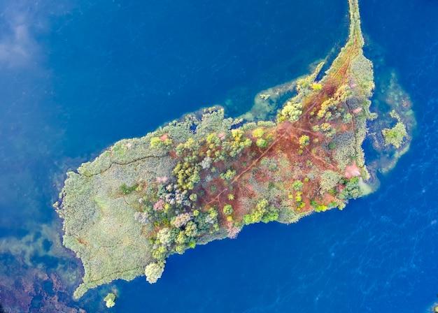 Mała wyspa na środku jeziora, na drzewach żółte jesienne liście. widok z drona.