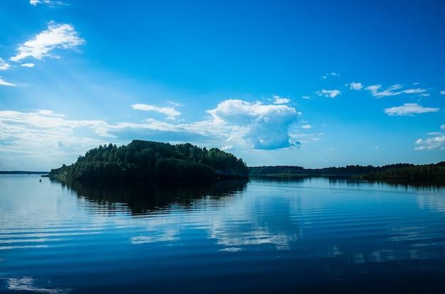 Mała wyspa pokryta drzewami wśród jeziora piękne błękitne niebo z chmurami i wodą