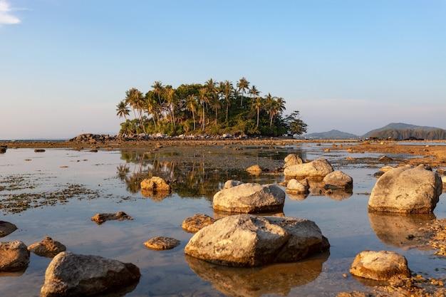 Mała wyspa w tropikalnym morzu zachód lub wschód słońca w dzień odpływu.