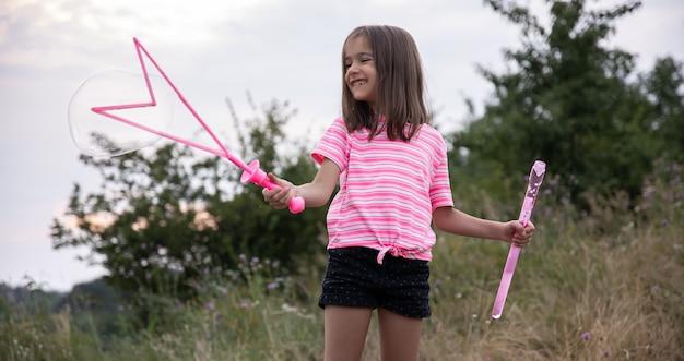 Mała zabawna dziewczyna wieje bańki mydlane latem w polu, letnie zajęcia na świeżym powietrzu.