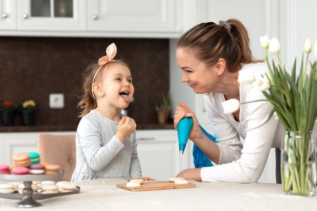 Mała zabawna dziewczynka i jej matka do pieczenia makaroników i ciastek w białej kuchni
