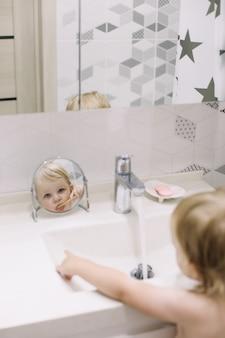 Mała zabawna dziewczynka myje zęby w łazience