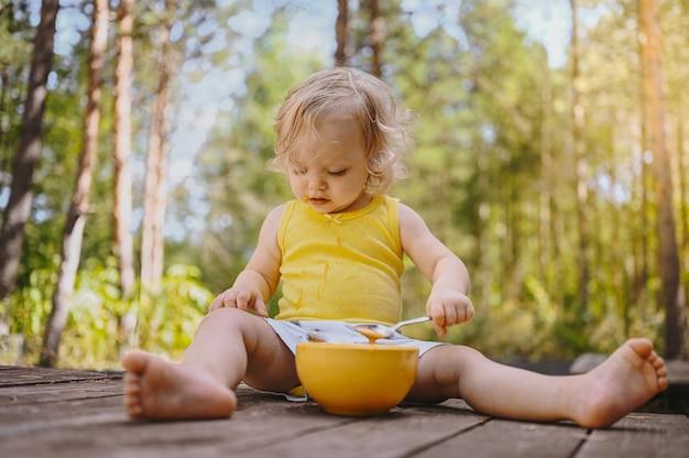Mała zabawna śliczna blond dziewczynka maluch z brudnymi ubraniami i twarzą jedząca owoce dla dzieci lub