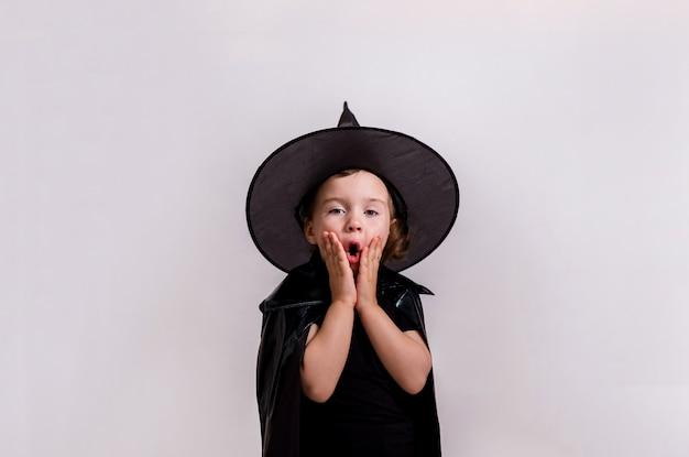 Mała zaskoczona dziewczyna w stroju czarownicy. koncepcja halloween