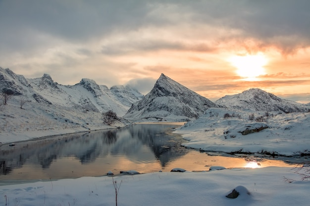 Mała zatoka norweskiego fiordu otoczona ośnieżonymi górami.