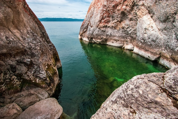 Mała zatoka otoczona klifami na jeziorze bajkał z zieloną przezroczystą wodą
