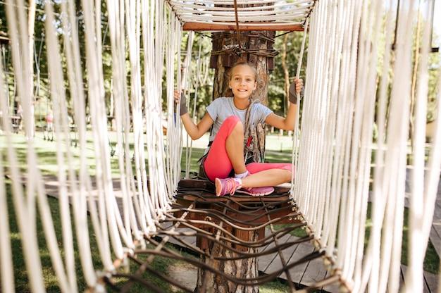 Mała żeńska wspinaczka w parku linowym, plac zabaw. dziecko wspinające się na wiszący most