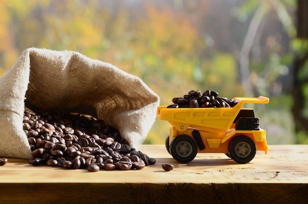 Mała żółta ciężarówka z zabawkami jest wypełniona brązowymi ziarnami kawy wokół pełnego worka z ziarnami.