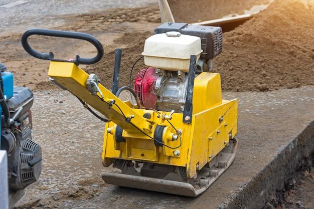 Mała żółta ręczna technika układania asfaltu.