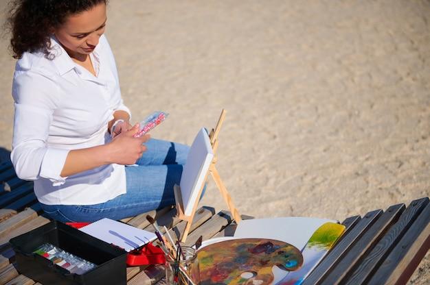 Malarka trzymająca pudełko z farbami, siedząca na drewnianym szezlongu na plaży z płótnem i paletą na nim