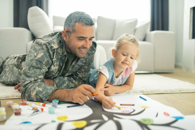 Malarstwo drzewo genealogiczne. przystojny szczęśliwy sługa wojskowy i jego córka razem malują drzewo genealogiczne