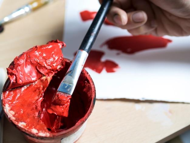 Malarz bierze czerwoną farbę za pomocą pędzla