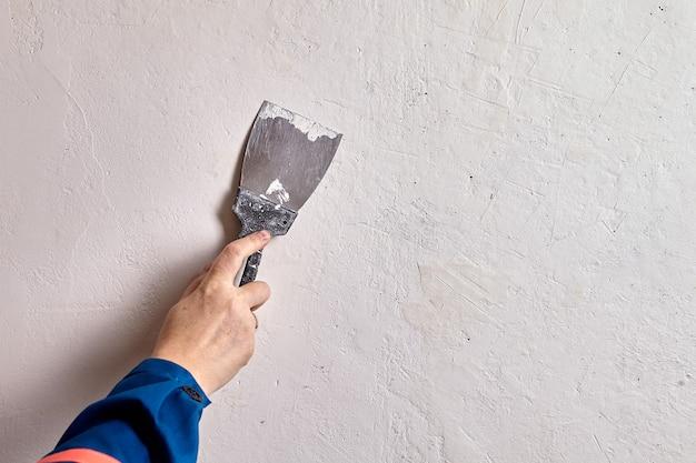 Malarz domowy łata mniejsze pęknięcia i dziury, naciska szpachlę szpachlową na niedoskonałości powierzchni, upewniając się, że szpachlówka wypełnia dziury lub pęknięcia.