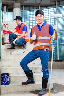 Malarz indonezyjski z azji maluje pędzlem, wałkiem, farbą i narzędziami w butach gumowych lub kaloszach i rękawicach ochronnych na ścianach wieżowca lub placu budowy