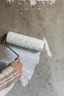 Malarz maluje betonową ścianę białą farbą, męska ręka wałkiem do malowania ściany
