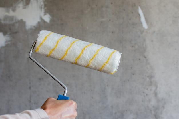 Malarz maluje betonową ścianę, męską dłoń wałkiem malarskim do malowania ściany