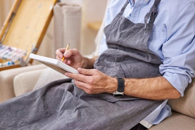 Malarz maluje ołówkiem na małym płótnie, szkicuje siedząc na sofie w fartuchu. przycięte