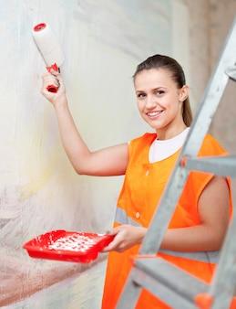 Malarz maluje ścianę rolką