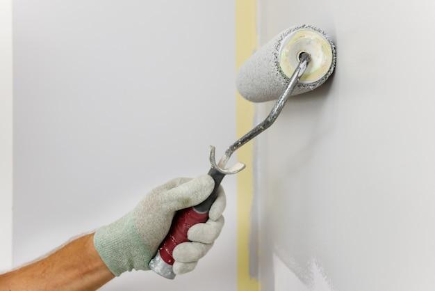 Malarz maluje wałkiem ścianę w pokoju.