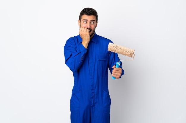 Malarz mężczyzna trzyma wałek do malowania na białym tle na białej ścianie nerwowy i przestraszony, wkładając ręce do ust