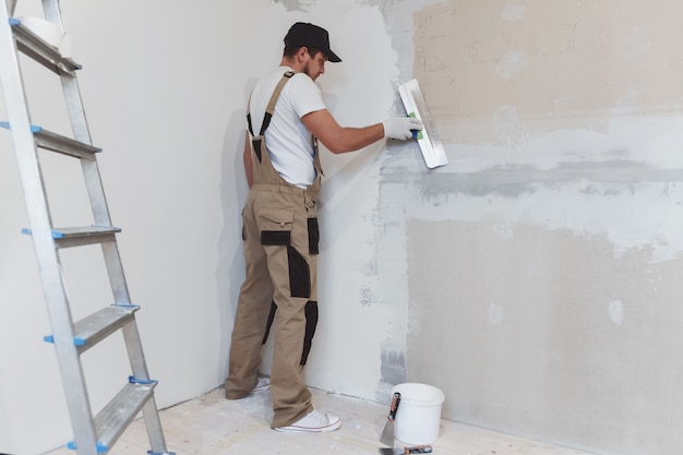 Malarz-mężczyzna ze szpatułką w dłoniach dokonuje napraw w domu. koncepcja renowacji pokoju.