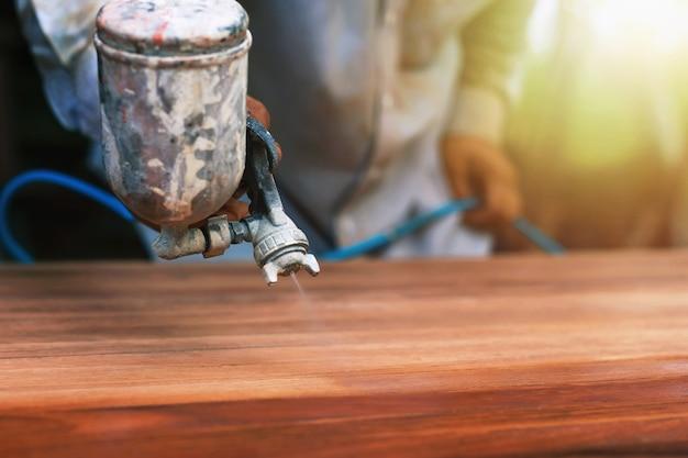 Malarz natryskuje kolor drewna, aby drewniana podłoga była piękna.