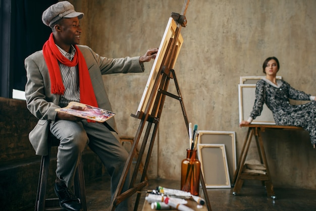 Malarz portret szczęśliwy z pędzlem rysuje modelki w studio sztuki. mężczyzna artysta w swoim miejscu pracy, kreatywny mistrz przy sztalugach w warsztacie