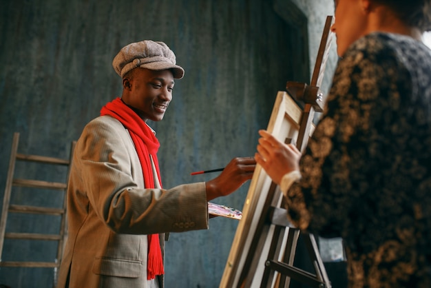 Malarz portretów przy sztalugach rysuje modelkę. mężczyzna artysta stojący w swoim miejscu pracy, twórczy mistrz pracuje w warsztacie