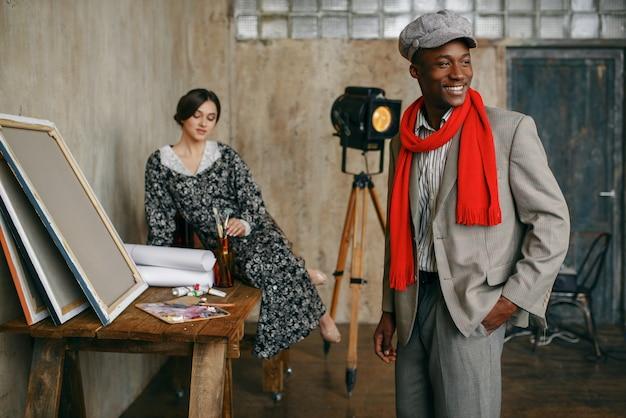 Malarz portretów w czerwonym szaliku i modelki w studio sztuki. mężczyzna artysta stojący w swoim miejscu pracy, kreatywny mistrz w warsztacie