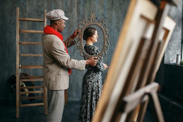 Malarz posiada ramę, modelki w studio sztuki. mężczyzna artysta stojący w swoim miejscu pracy, kreatywny mistrz w warsztacie