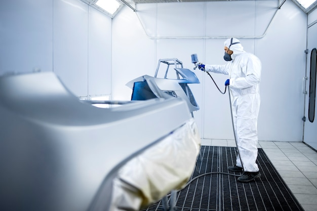 Malarz samochodowy w odzieży ochronnej i maski malowanie zderzaków samochodowych farbą metaliczną i lakierem w warsztacie komorowym.