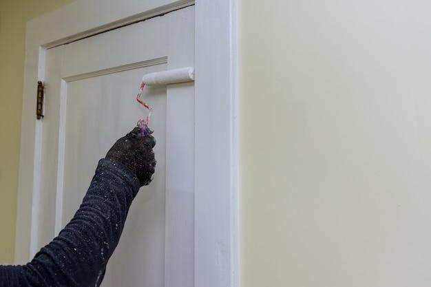 Malarz wykonawca aktualizujący kolorystykę malowania drzwi za pomocą ręcznego malowania wałkiem w rękawiczkach