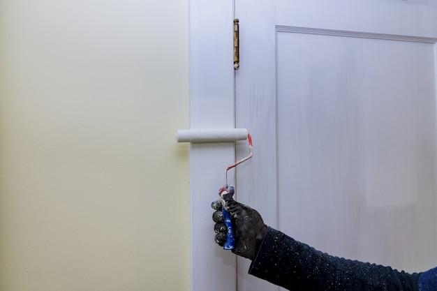 Malarz wykonawca aktualizuje kolory malowania listew drzwiowych za pomocą ręcznego malowania wałkiem