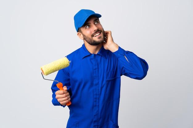 Malarza mężczyzna trzyma farba rolownika odizolowywającego na bielu myśleć pomysł