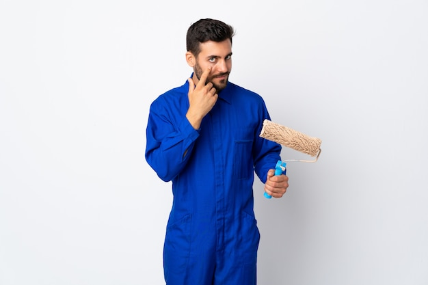 Malarza mężczyzna trzyma farba wałek odizolowywający na biel ścianie pokazuje coś