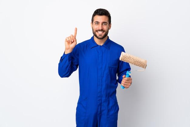 Malarza mężczyzna trzyma farba wałek odizolowywający na bielu wskazuje w górę doskonałego pomysłu