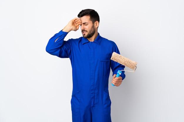 Malarza mężczyzna trzyma farba wałek odizolowywający na bielu z zmęczonym i chorym wyrażeniem