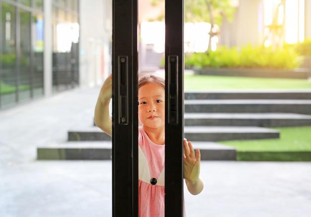 Małe azjatyckie dzieci otwierają szklane drzwi przed salonem.