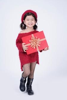 Małe azjatyckie dziecko w czerwonej sukience trzyma czerwone pudełko na boże narodzenie