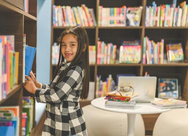 Małe azjatyckie dziecko zbierając książki z półki na książki