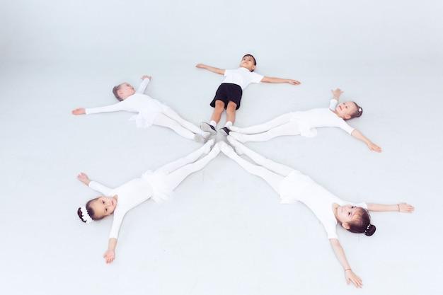 Małe baleriny dziewczęta i chłopiec robią podziały na białej przestrzeni na podłodze